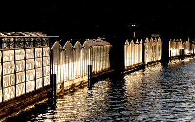 Lit fence surrounding the water wallpaper