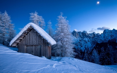 Old barn in the mountains surrounded by snow wallpaper