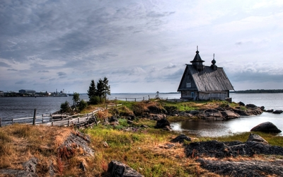 Old small house on the rocky river shore Wallpaper