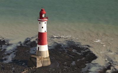 Red and white lighthouse surrounded by water wallpaper