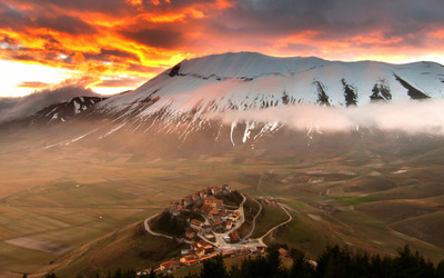 Small town on top of the hill by the snowy mountains wallpaper