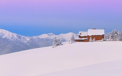 Wooden house on a snowy mountain wallpaper